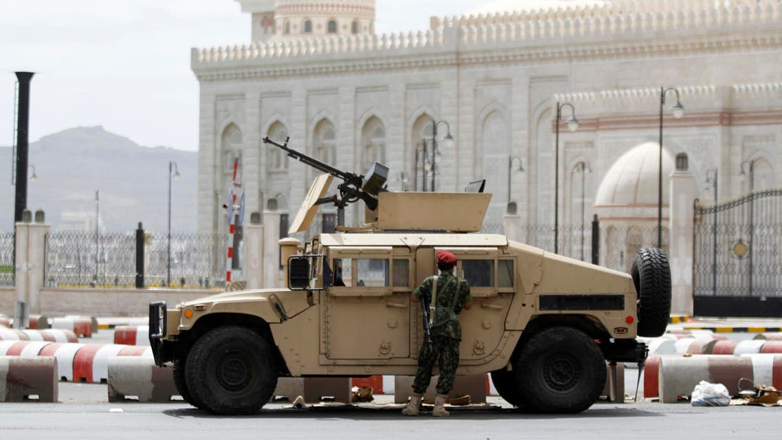 A soldier stands next to a military vehicle blocking al-Sabeen street, which leads to the presidential palace in Sanaa May 10, 2014.  (Reuters)