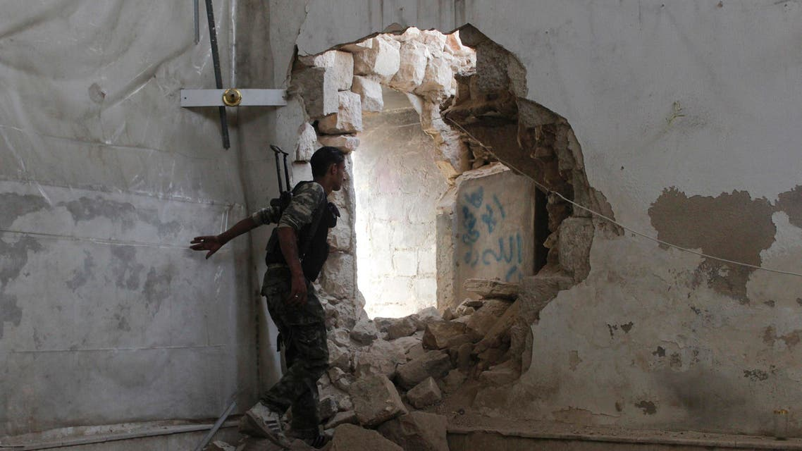 A Free Syrian Army fighter goes through a hole in the wall heading towards the frontline in Old Aleppo May 31, 2014.
