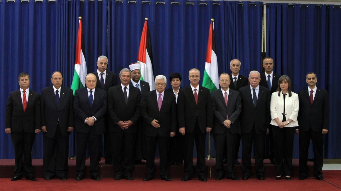 Palestinian president Mahmud Abbas (C) poses for a picture with the members of the new Palestinian unity government in the West Bank city of Ramallah June 2, 2014.