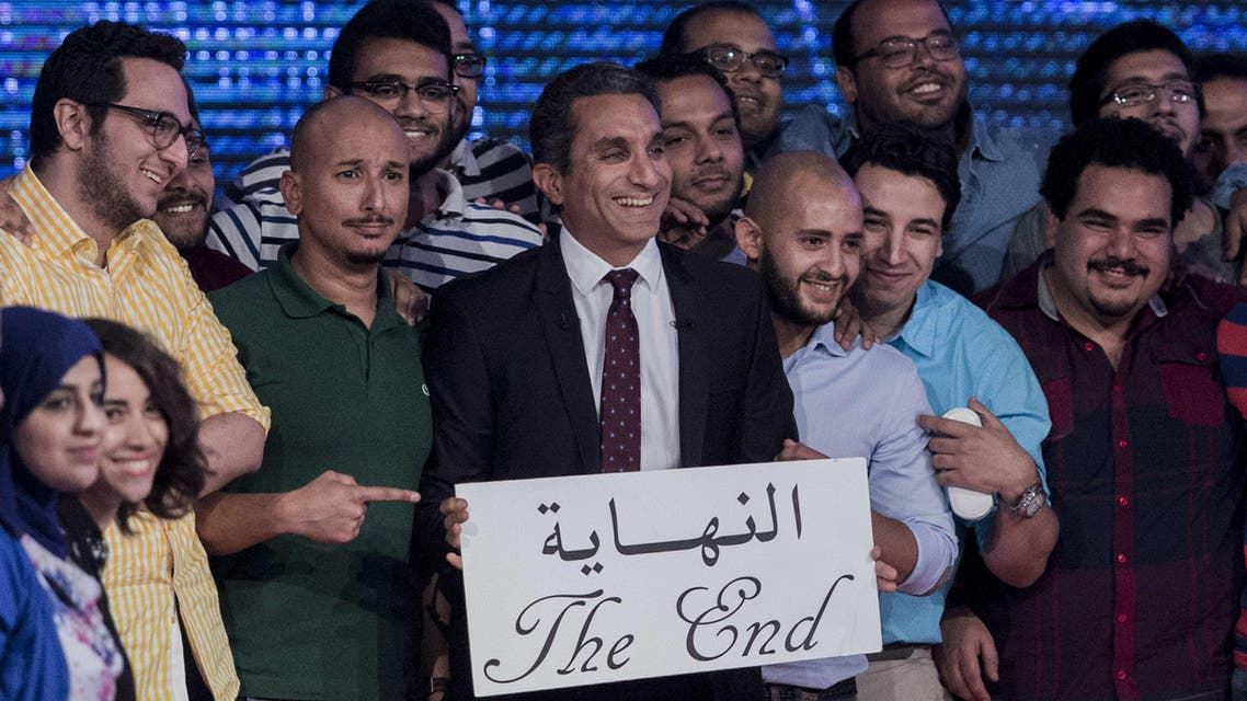 """Egyptian satirist and television host Bassem Youssef (C) and his team hold a placard reading in Arabic """"the end"""" during a press conference to announce the end of his TV show on June 2, 2014 in the capital Cairo. (AFP)"""
