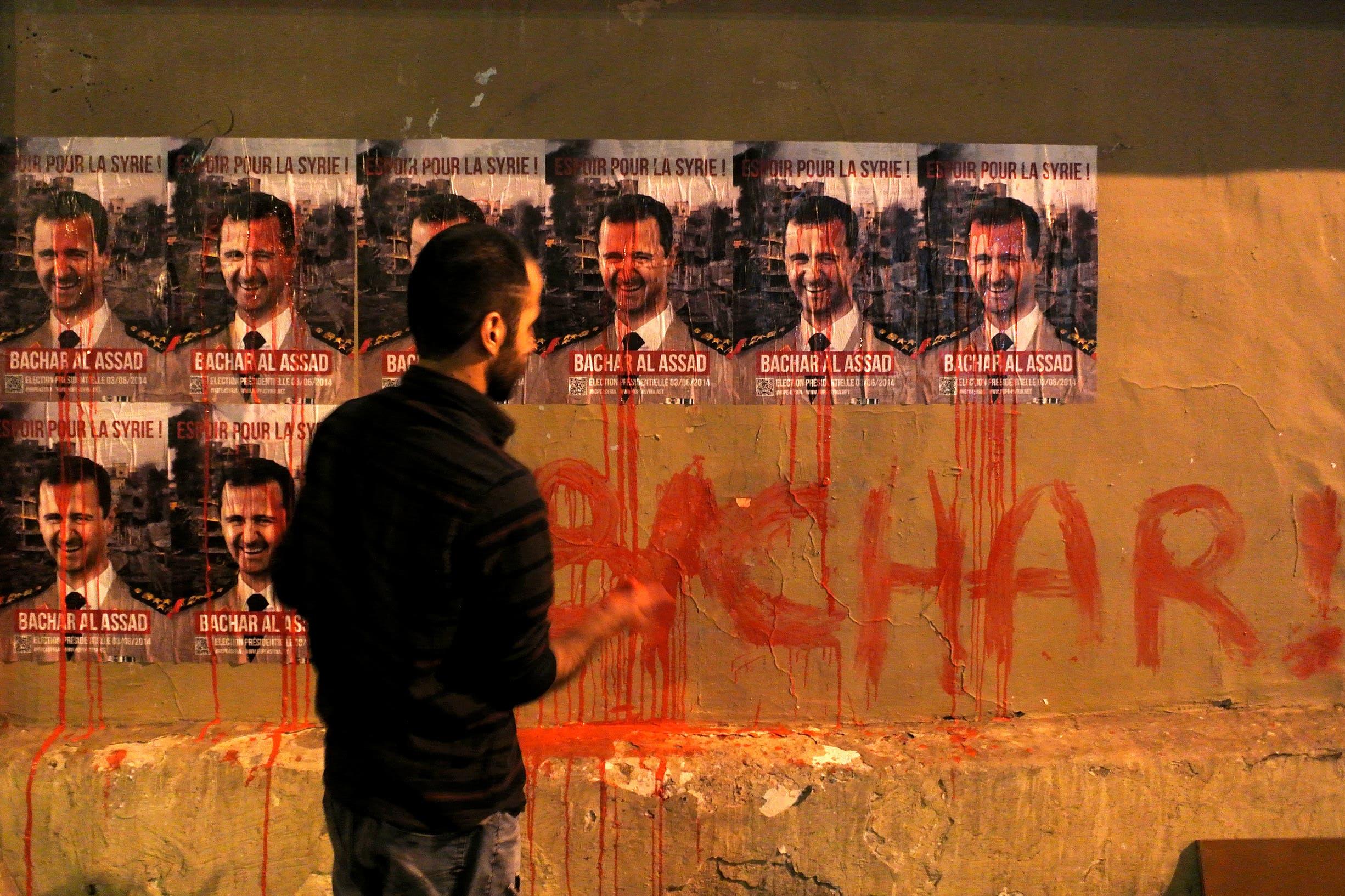 ملصقات على جدران باريس تسخر من بشار الأسد