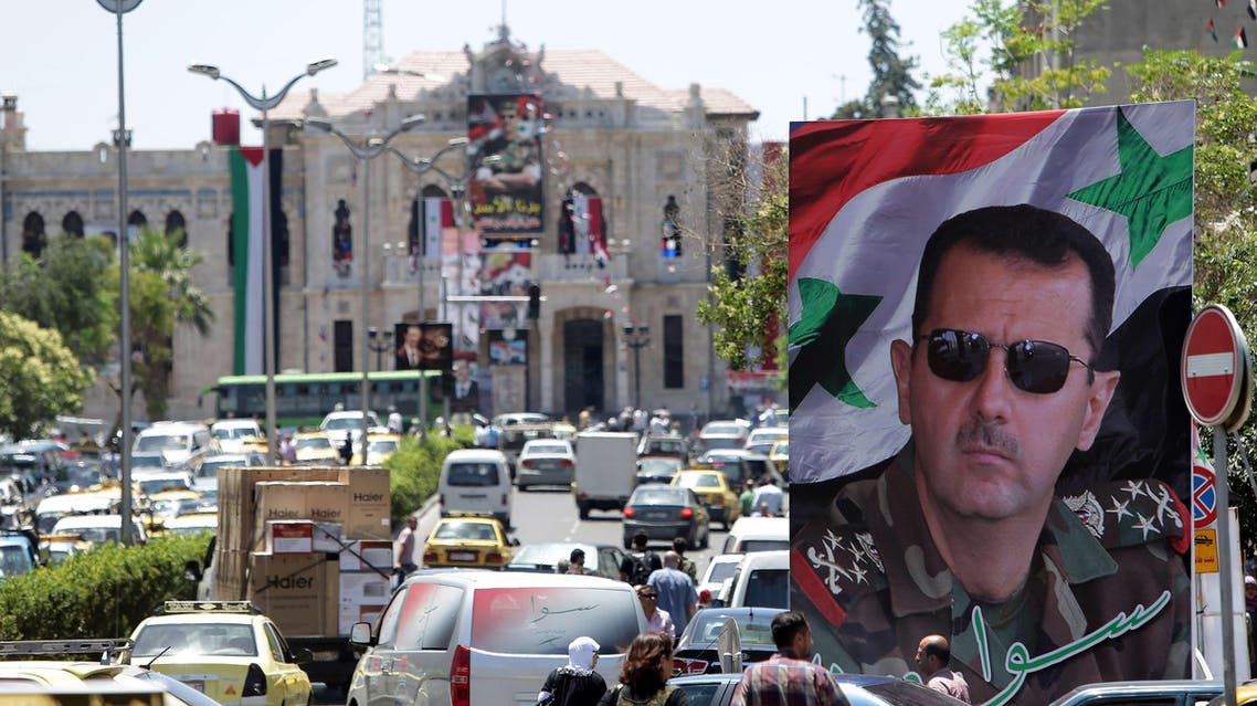 Syrians drive their vehicle past a campaign billboard bearing the portrait of Syrian President Bashar al-Assad on June 1, 2014 in the capital Damascus