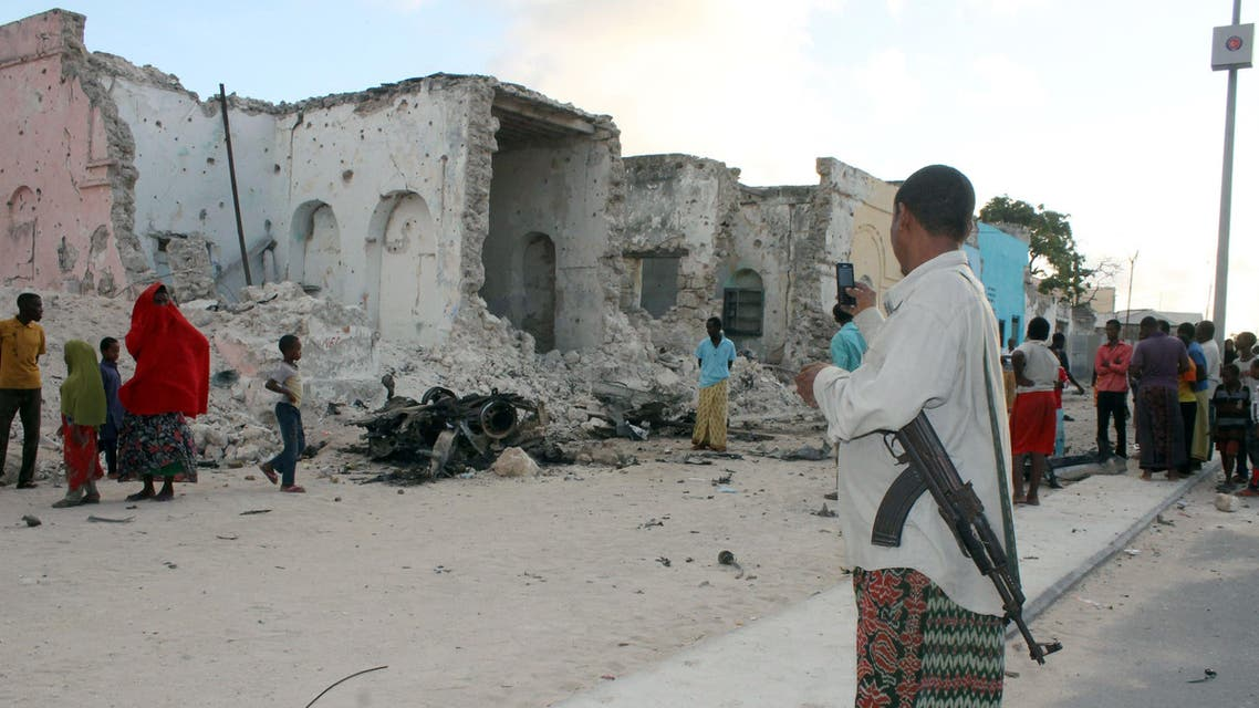 A Somali soldier takes a picture with his mobile phone of an explosion site on May 31, 2014. (AFP)