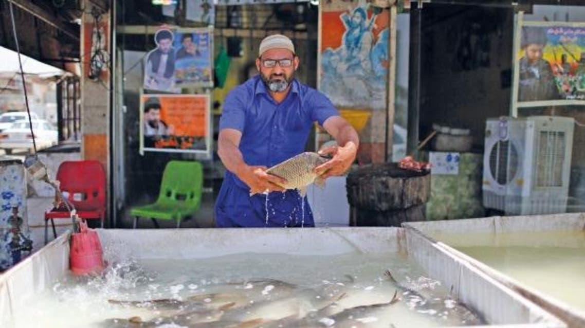 عامل عراقي يعمل في بيع الأسماك