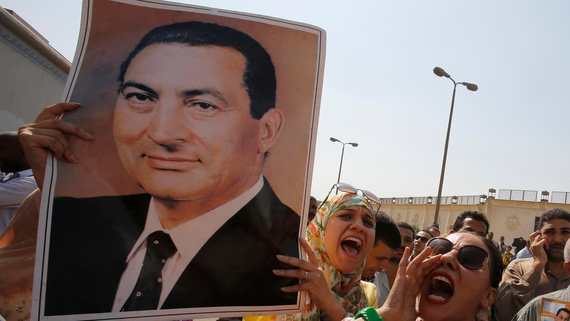 Supporters of former president Hosni Mubarak hold his poster to celebrate his release in front of the main gate of Tora prison on the outskirts of Cairo August 22, 2013.  (Reuters)