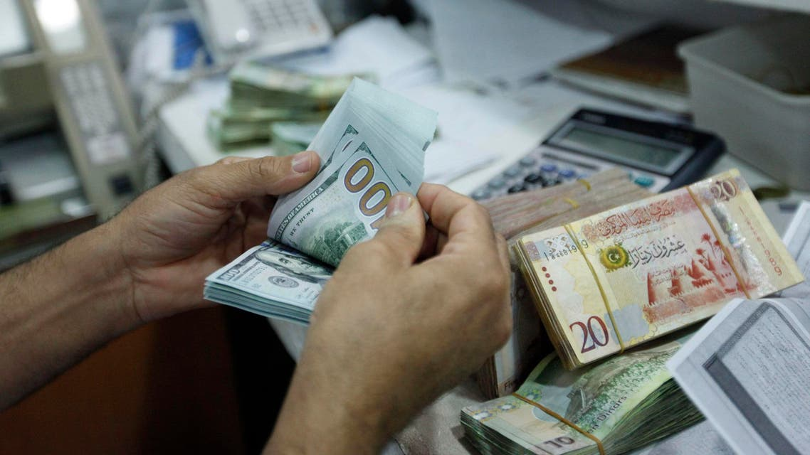 A man counts U.S. dollars at a currency exchange office in central Tripoli, June 3, 2014. (Reuters)