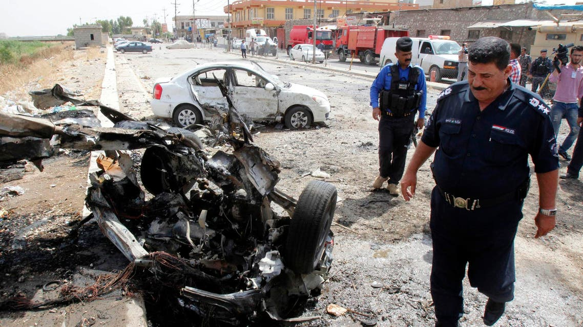 Iraqi security forces inspect the site of a car bomb attack in Kirkuk, June 4, 2014. (Reuters)