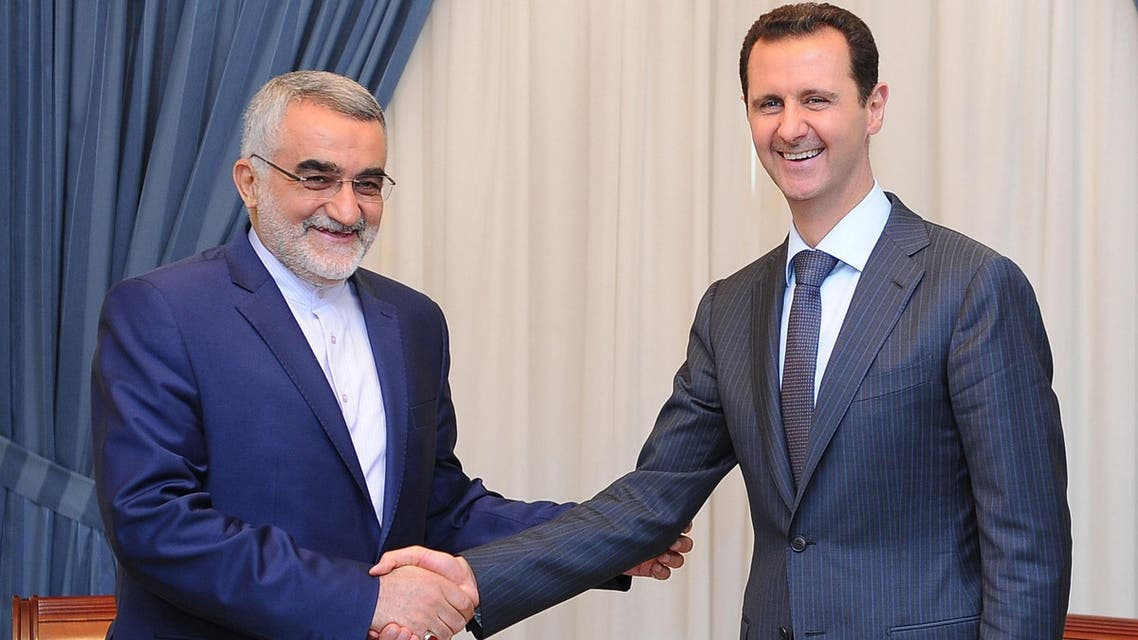 Syrian President Bashar al-Assad (R) shaking hands with The Chairman of the Foreign Policy and National Security Committee at the Iranian Shura Council, Alaeddin Boroujerdi in Damascus on June 5, 2014. (AFP)