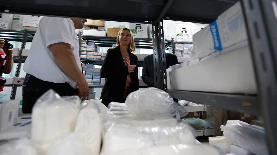 Italian Foreign Minister Federica Mogherini (C) listens to explanations by members of Red Cross and Red Crescent during her visit to a Syrian refugee camp east of Amman, June 8, 2014. (Reuters)