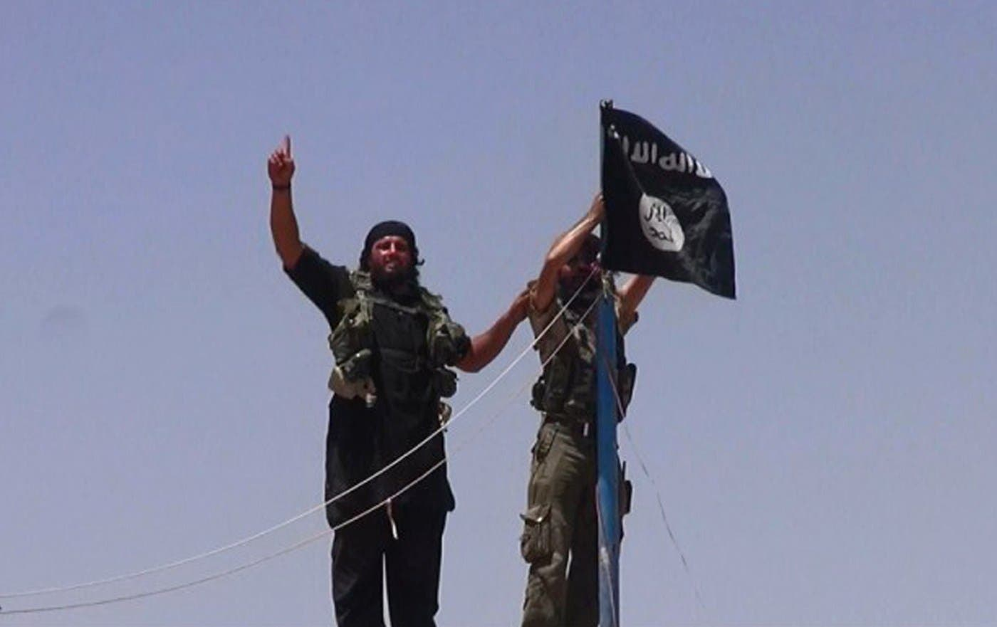 ISIS Militants hanging the Islamic Jihad flag on a pole at the top of an ancient military fort after they cut a road through the Syrian-Iraqi border. (AFP)