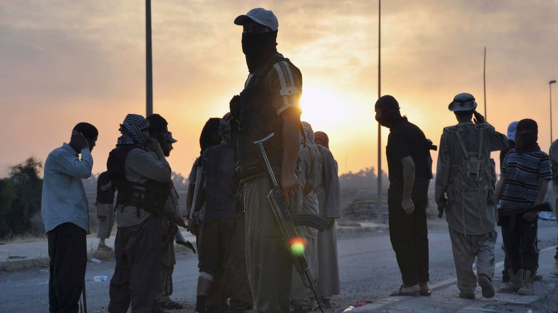 Fighters of the Islamic State of Iraq and the Levant (ISIL) stand guard at a checkpoint in the northern Iraq city of Mosul, June 11, 2014. (Reuters)
