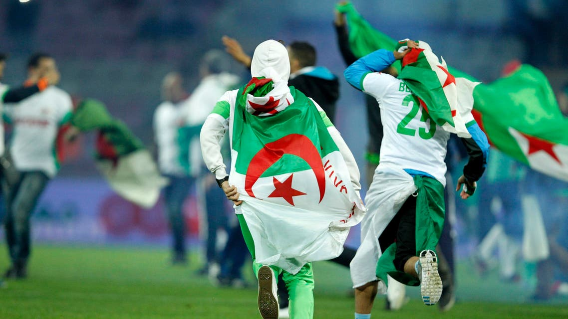 Algeria supporters wearing the Algerian national flag celebrate at a friendly. (Reuters)