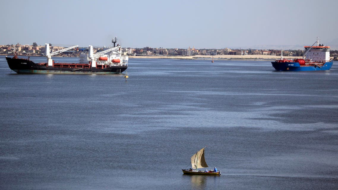 A fisherman travels on a boat front of container ships in the Suez canal near Ismailia port city, northeast of Cairo May 2, 2014. (Reuters)