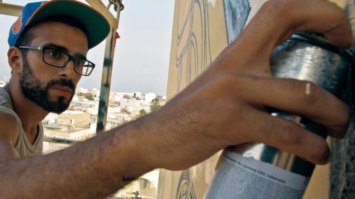 ان فرنسي شاب من أصل تونسي منذ أسبوع لوحة جدارية تجمع بين الغرافيتي والخط العربي على إحدى واجهات معهد العالم العربي في باريس