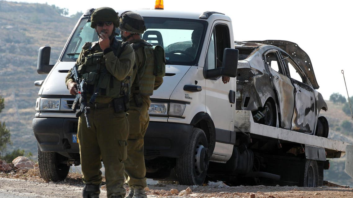 Israeli soldiers secure the area around a burnt car (background) on June 13, 2014, reportedly connected to the disappearance of three Israeli teen settlers in the West Bank town of Hebron.  (AFP)