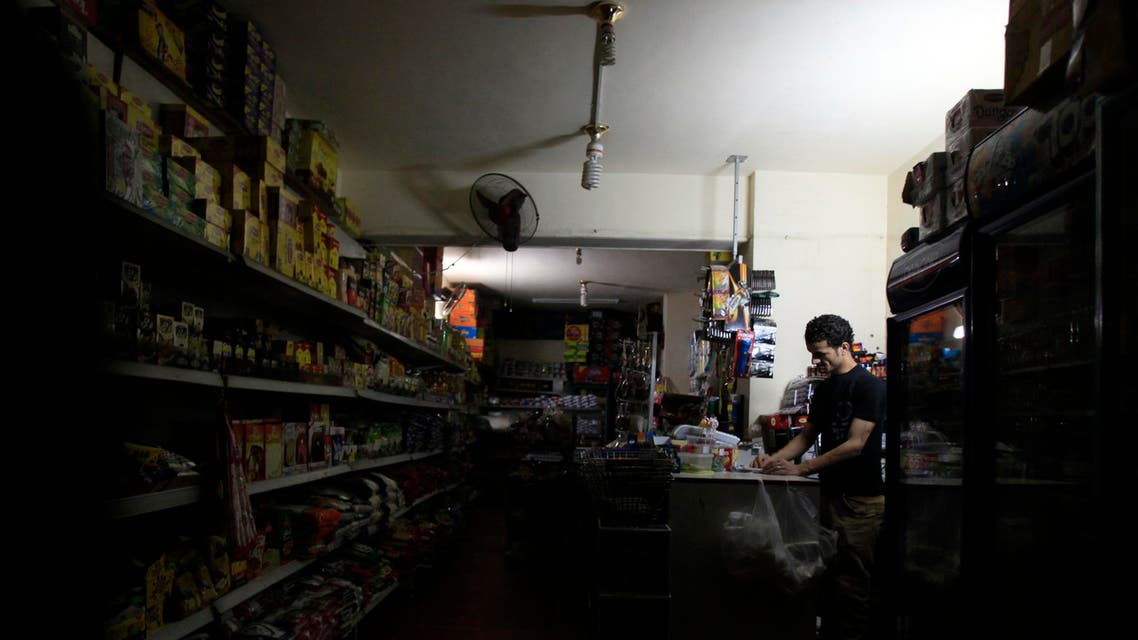 A supermarket seller stands near an emergency light during power outage at his shop in Cairo April 16, 2014. (Reuters)