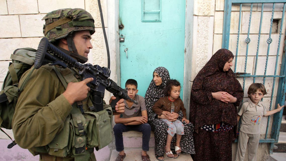 An Israeli soldier walks past Palestinians in the West Bank village of Tafoh, near Hebron on June 15, 2014
