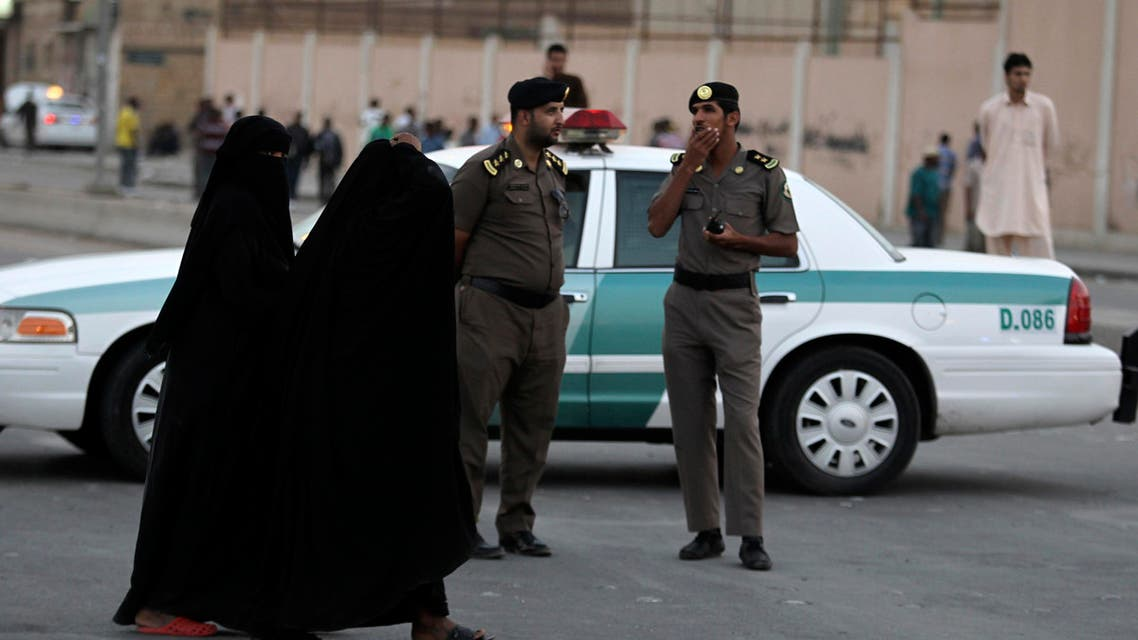 Women walk past members of Saudi security forces as they keep guard in Manfouha, southern Riyadh, November 14, 2013.