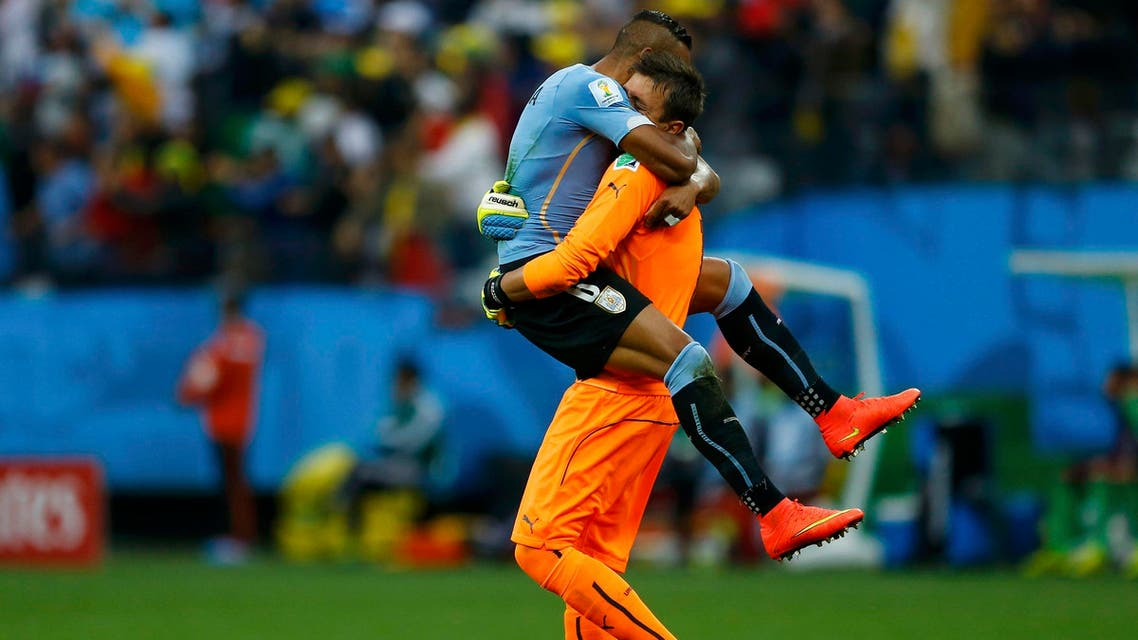 Uruguay's Jose Maria Gimenez (top) hugs teammate Fernando Muslera after Luis Suarez (unseen) scored against England during their 2014 World Cup Group D soccer match at the Corinthians arena in Sao Paulo June 19, 2014.