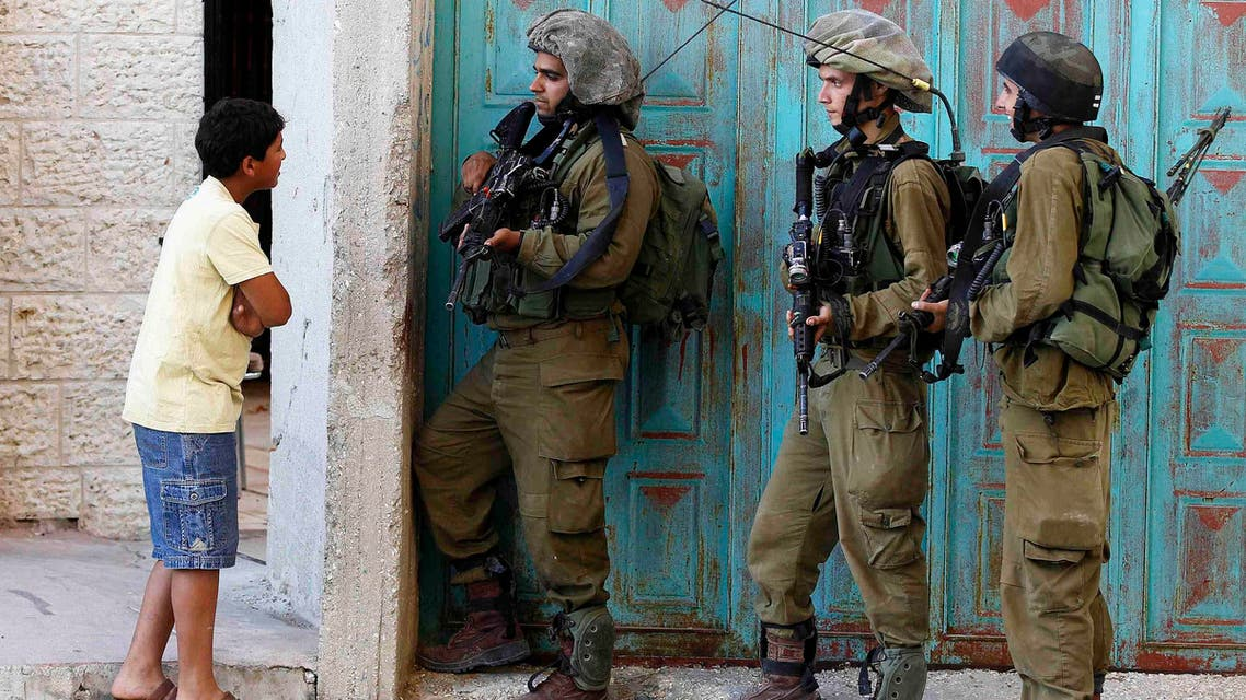 A Palestinian boy stands next to Israeli soldiers as they take part in an operation to locate three Israeli teens near the West Bank City of Hebron June 21, 2014.