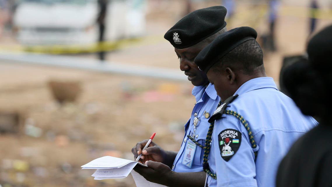 Policemen take down evidence at the scene of a car bomb attack in Nyanya, Abuja, May 2, 2014. reuters
