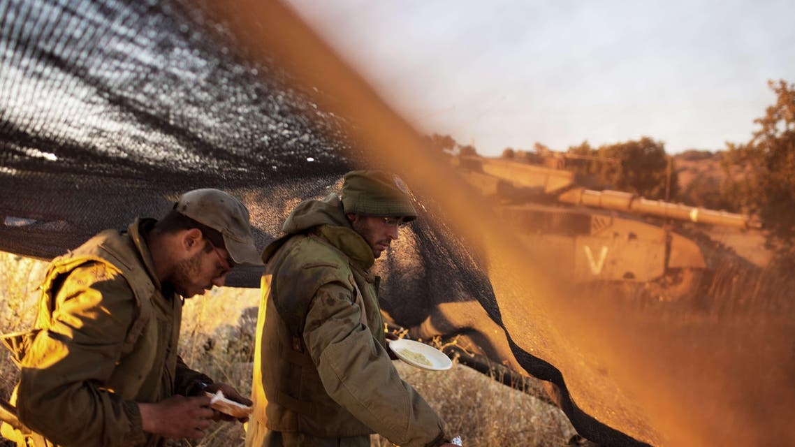 Israeli soldiers help themselves with food while positioned near the Quneitra checkpoint on the border with Syria in the Israeli-annexed Golan Heights, on June 22, 2014.  AFP