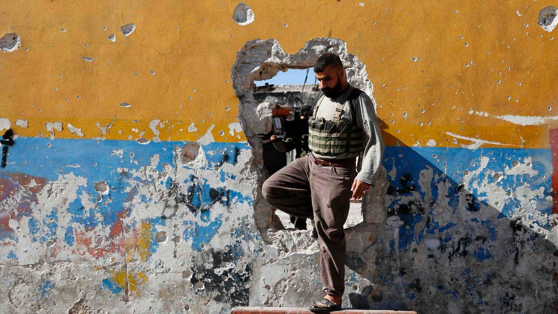 A rebel fighter walks through a hole in a wall on the frontline of Ramouseh, an area located beside Aleppo Artillery school June 22, 2014.  (Reuters)