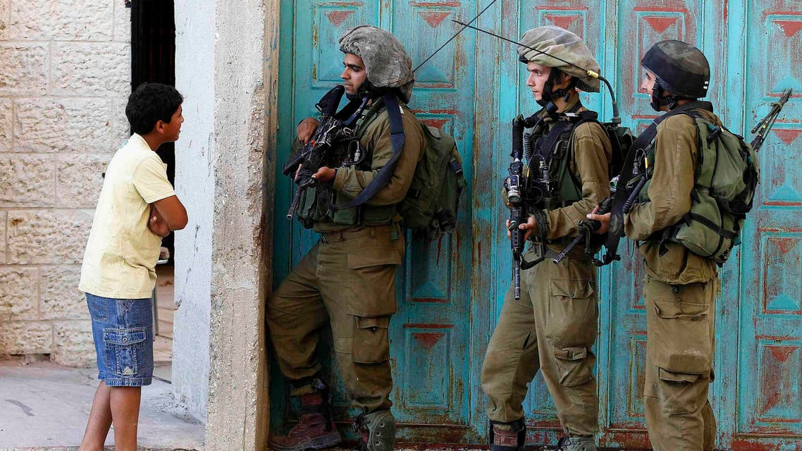 A Palestinian boy stands next to Israeli soldiers as they take part in operation to locate three Israeli teens near the West Bank City of Hebron Reuters