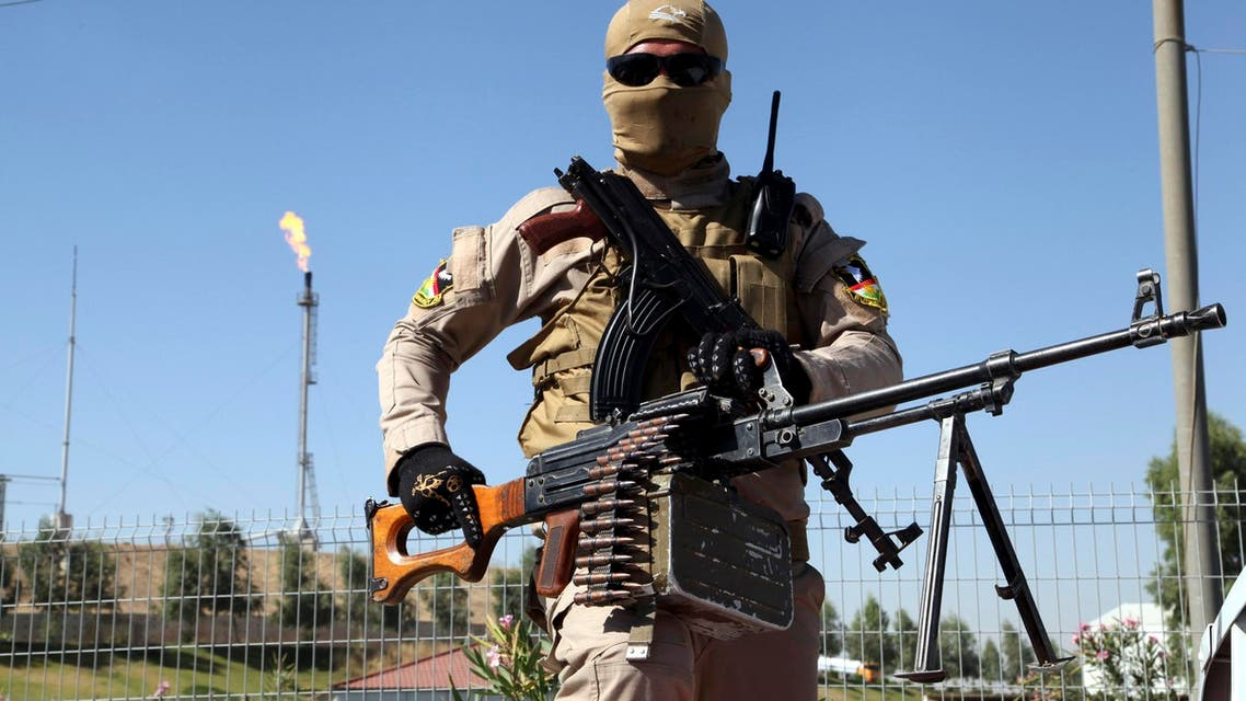 A member of the Kurdish security forces takes up position with his weapon while guarding an oil refinery, on the outskirts of Mosul, June 22, 2014. Reuters