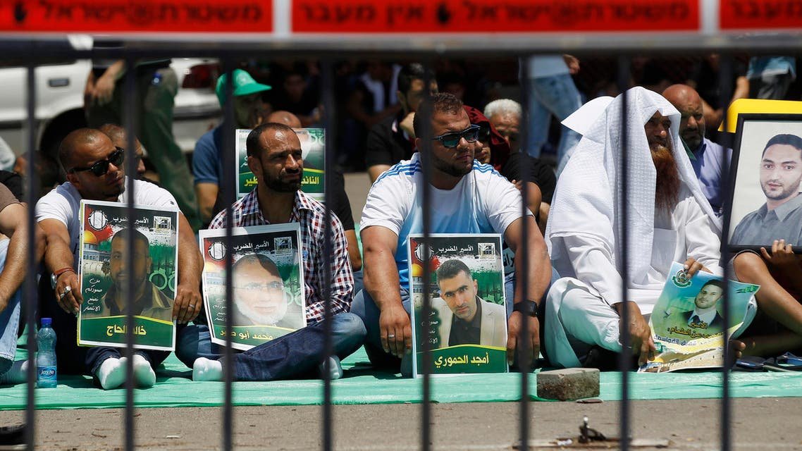 Relatives and friends of Palestinians jailed in Israeli prisons hold placards as they take part in a protest calling for the prisoners release outside the Ayalon prison, in Ramle, near Tel Aviv May 23, 2014. (Reuters)