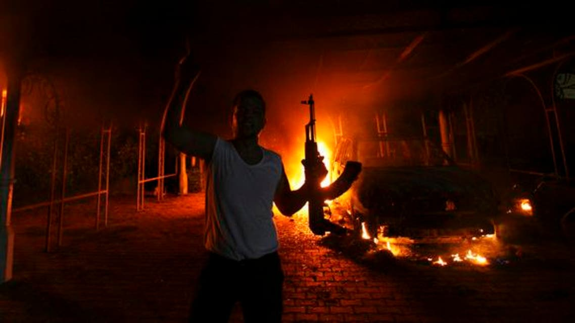A protester reacts as the U.S. Consulate in Benghazi is seen in flames during a protest by an armed group said to have been protesting a film being produced in the United States Sept. 11, 2012. (Reuters)