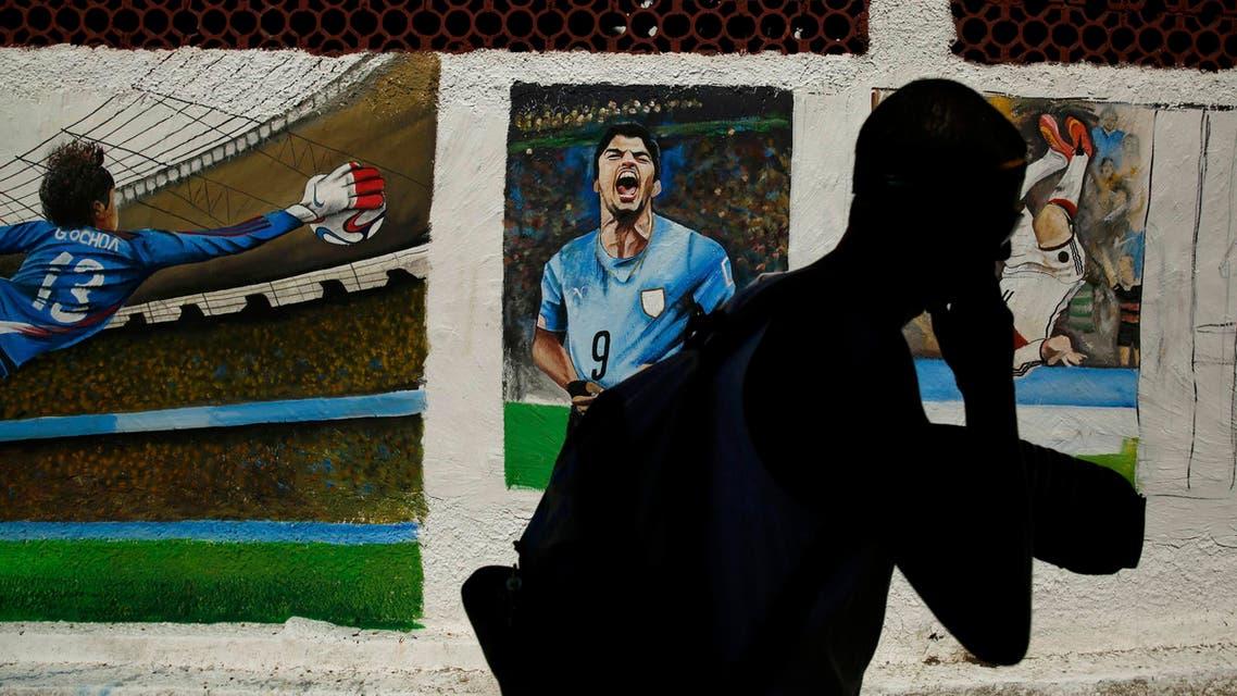 A man walks past murals of Mexico's goalkeeper Guillermo Ochoa and Uruguay's Luis Suarez on the Copacabana beach in Rio de Janeiro, June 27, 2014. (Reuters)