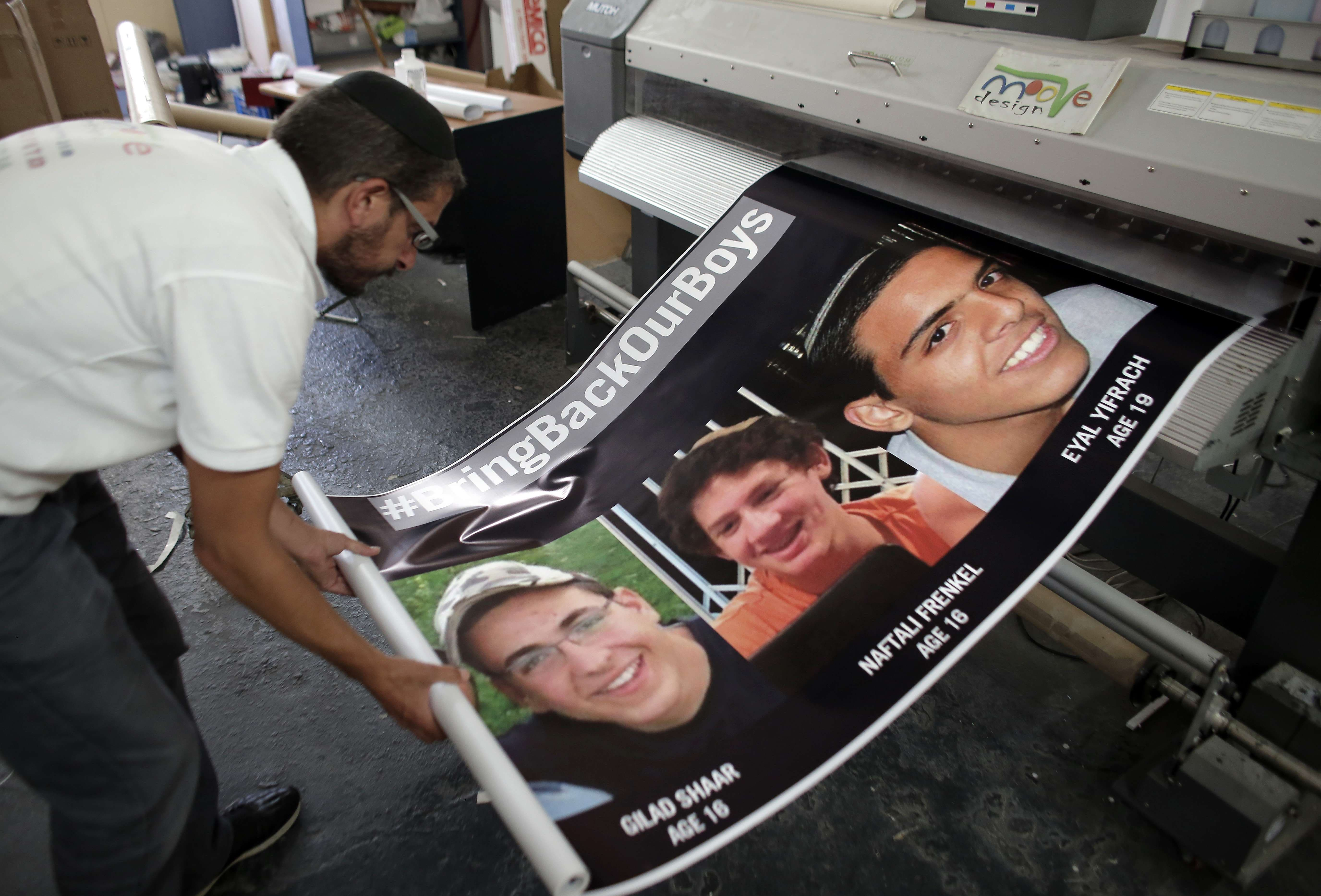 An Israeli printer finalizes posters in Jerusalem on June 23, 2014, of the three youth Israelis who disappeared from a hitchhiking stop in the southern West Bank on June 12. (AFp)