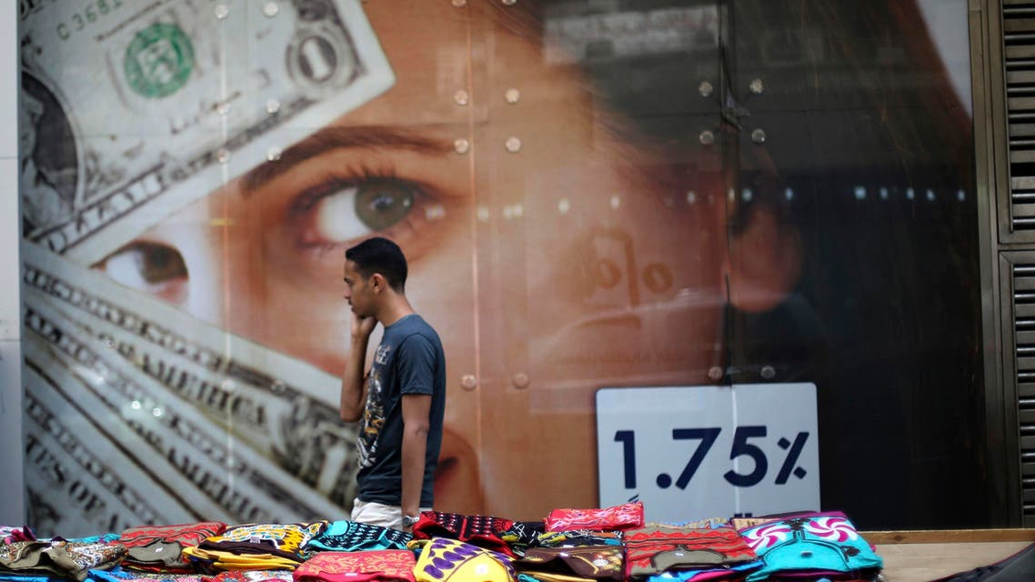 A pedestrian walks past a currency exchange shop and street stalls after Abdel Fattah al-Sisi took more than 90 percent of the vote in a presidential election, according to provisional results, in Cairo, May 29, 2014. (Reuters)