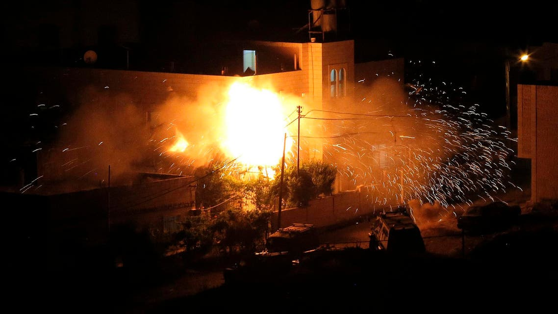 Flames are seen after a blast on the top floor of the family home of an alleged abductor in the West Bank City of Hebron July 1, 2014. reuters