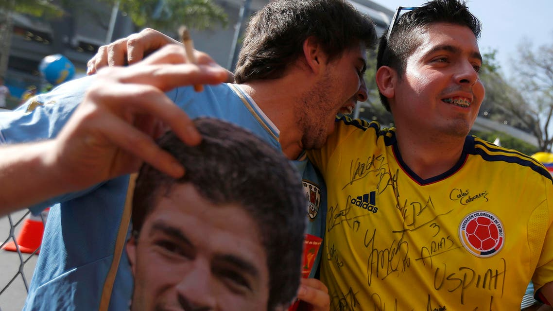 A fan of Uruguay (L) holds a mask of Luis Suarez as he jokes with a fan of Colombia before their 2014 World Cup round of 16 game at the Maracana stadium in Rio de Janeiro June 28, 2014. (Reuters)