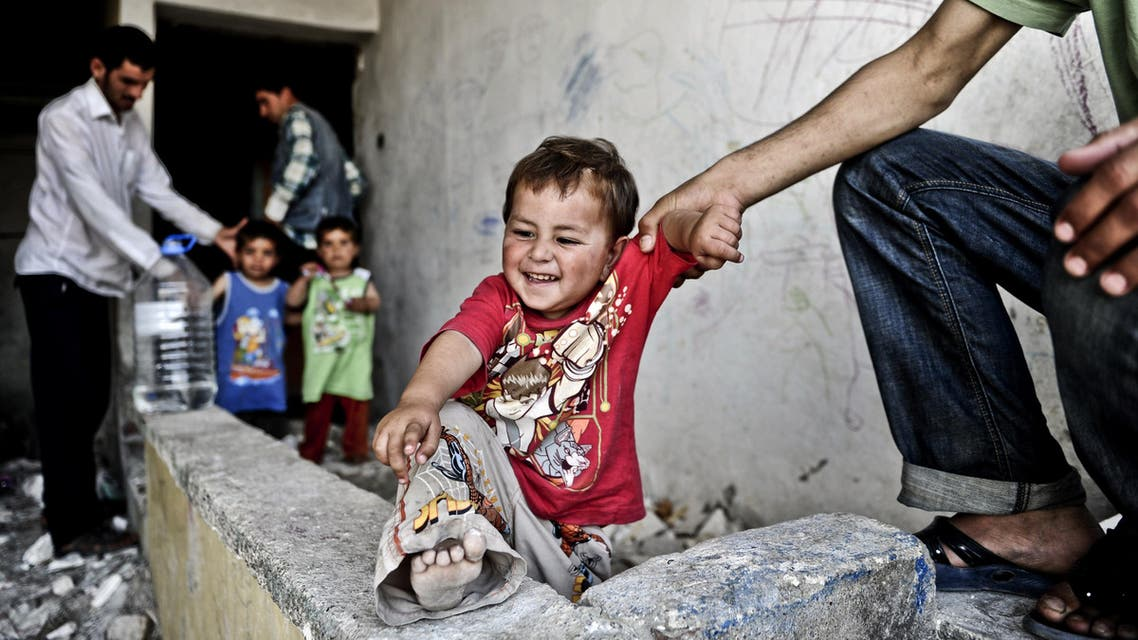 A Syrian man holds his infant in front of a disused house on June 28, 2014 in the Fikirtepe area of Istanbul. AFP