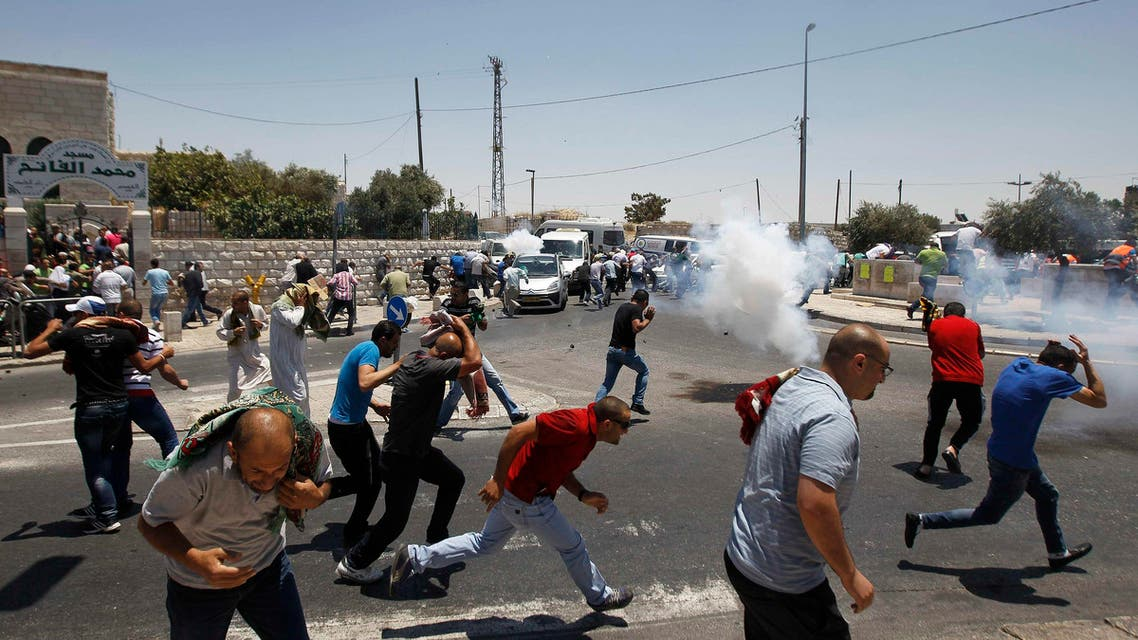 Palestinian protesters run away from tear gas fired by Israeli soldiers during clashes after Friday prayers in the Arab east Jerusalem neighbourhood of Ras al-Amud July 4, 2014. Reuters