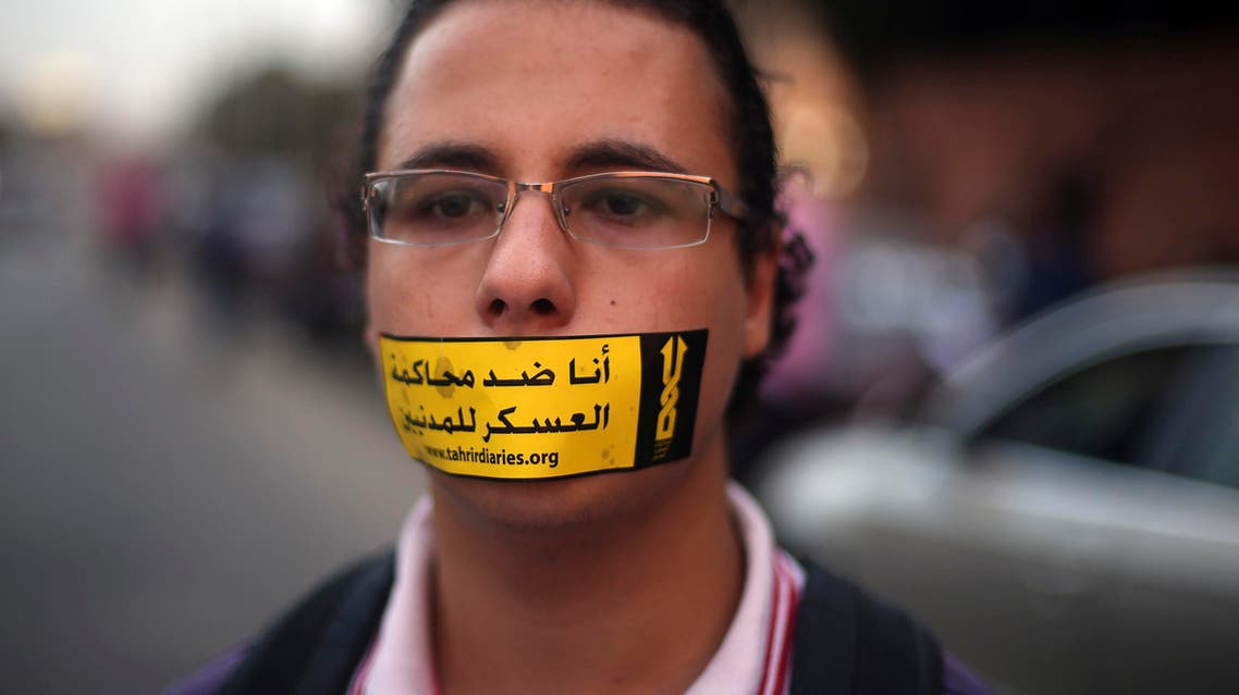 """A demonstrator looks on with a sign reading """"I am against the military courts for civilians"""" taped over his mouth during a human chain by members of the April 6 movement and liberal activists against the protest law. (Reuters)"""