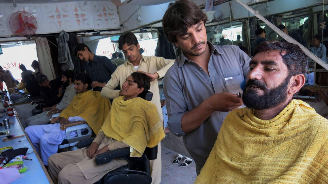 Internally displaced Pakistan civilians fleeing from a military operation against Taliban militants in the North Waziristan tribal agency receive haricuts at a barbershop in the neighbouring town of Bannu on July 6, 2014.