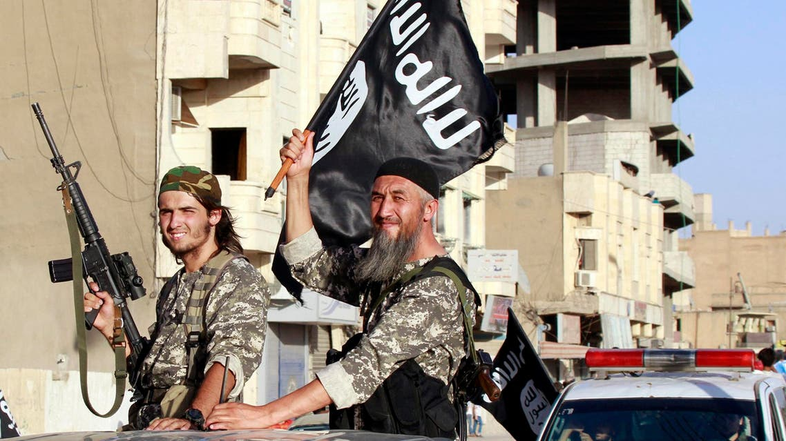 Militant Islamist fighters wave flags as they take part in a military parade along the streets of Syria's northern Raqqa province June 30, 2014.