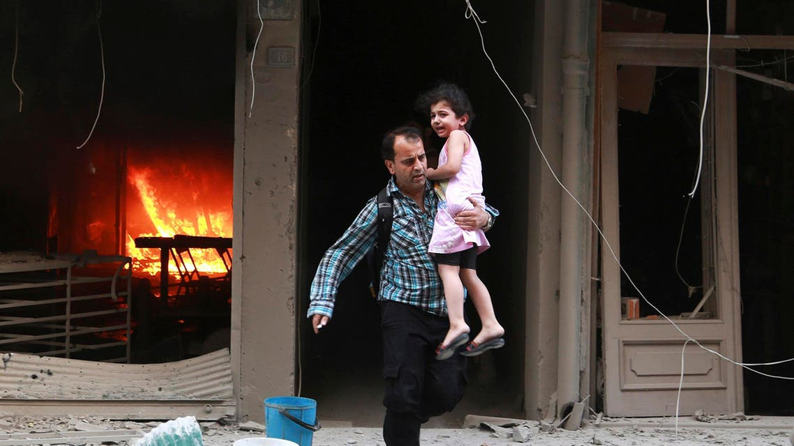 A man carrying a child runs out of a burning building at a site hit by what activists said were barrel bombs dropped by forces of Syria's President Bashar al-Assad in Aleppo's al-Shaar district July 9, 2014.  (Reuters)