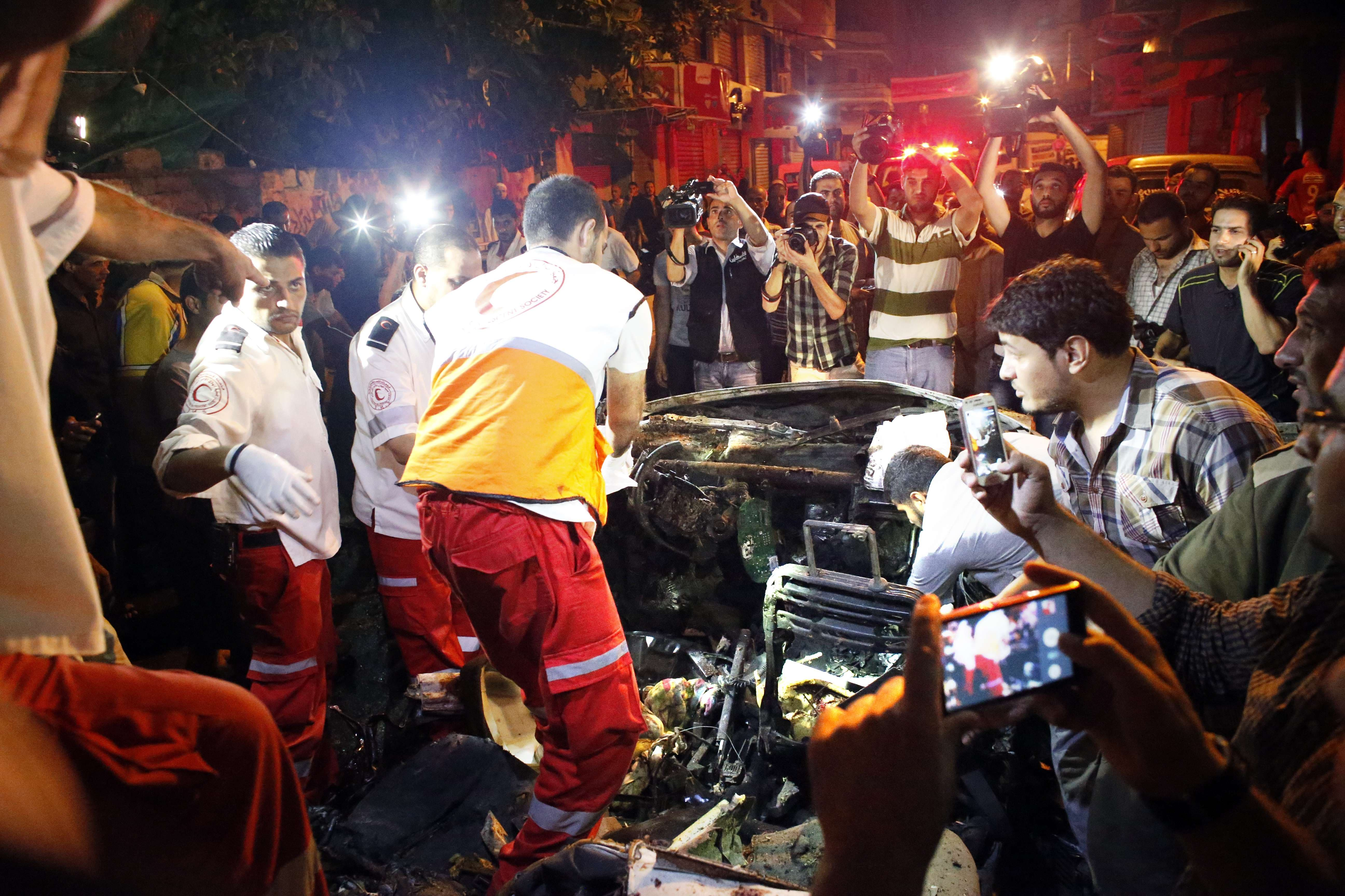 Palestinian rescuers check a car hit by an Israeli air strike killing the driver in Gaza City on July 9, 2014. afp