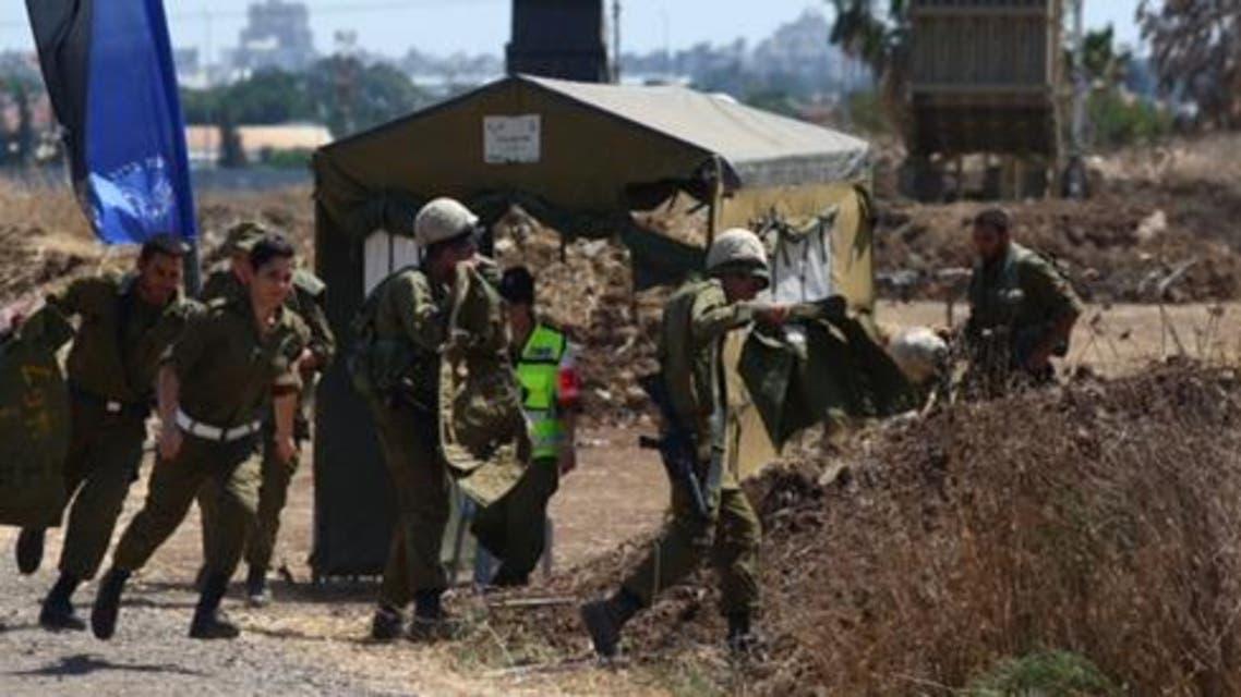 جنود في الجيش الاسرائيلي يحتمون اثناء اطلاق صواريخ من غزة على قاعدتهم