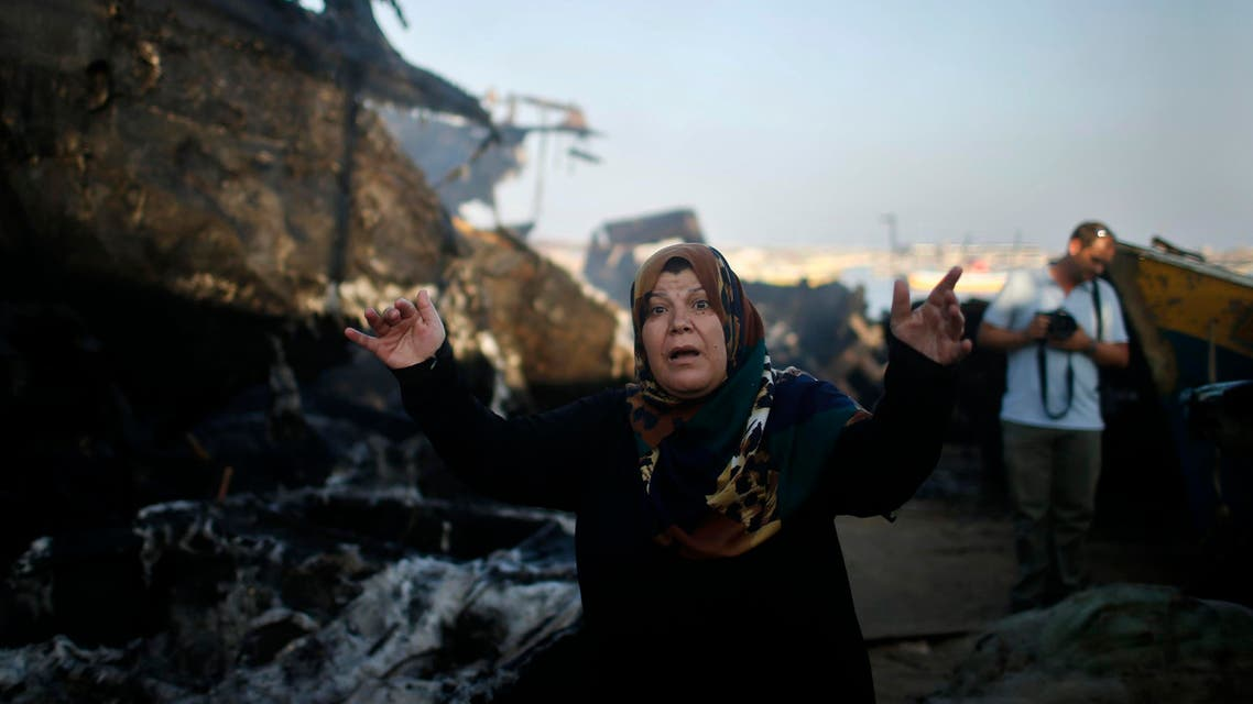 A Palestinian woman reacts in front of her son's boat, which police say was damaged in a fire that started following an Israeli naval strike, at the seaport of Gaza City July 11, 2014. (Reuters)