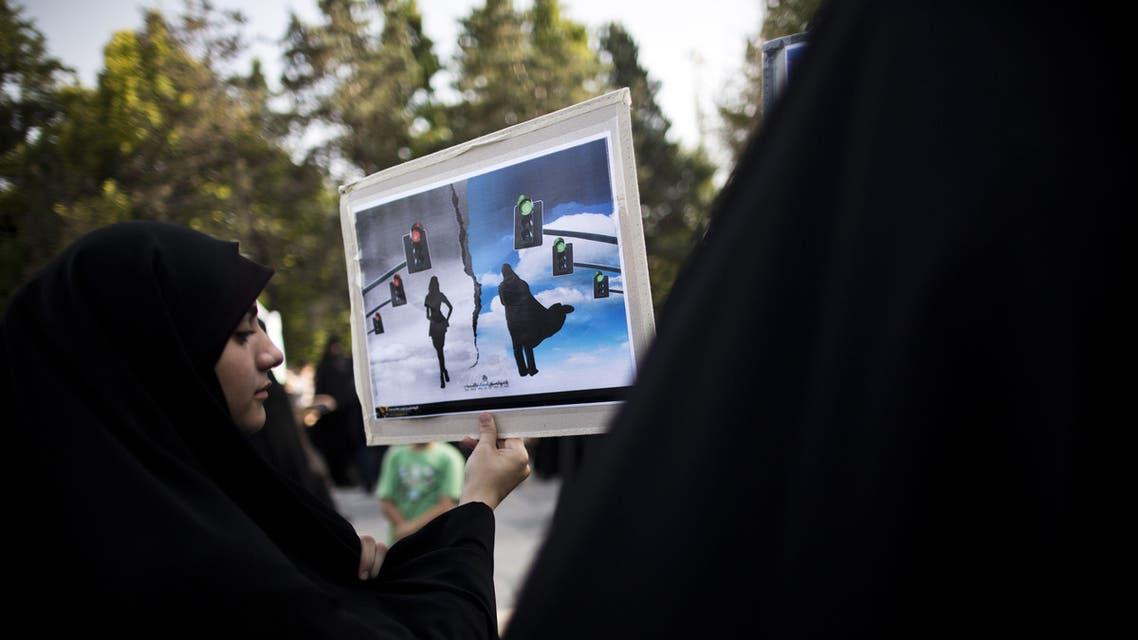 An Iranian hardliner woman holds a placard during a protest to ask for the revival of the islamic hijab and chastity in Iranian state TV programs on July 12, 2014 in Tehran. (AFP)