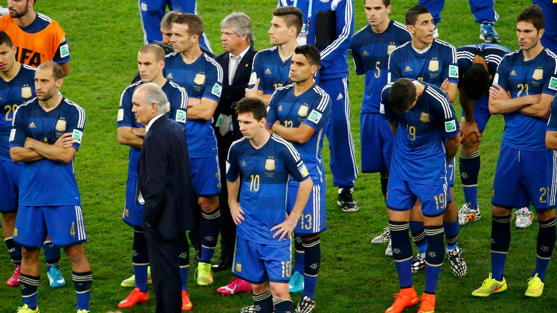 Argentina's coach Alejandro Sabella stands between his players after their loss to Germany in their 2014 World Cup final at the Maracana stadium in Rio de Janeiro July 13, 2014.