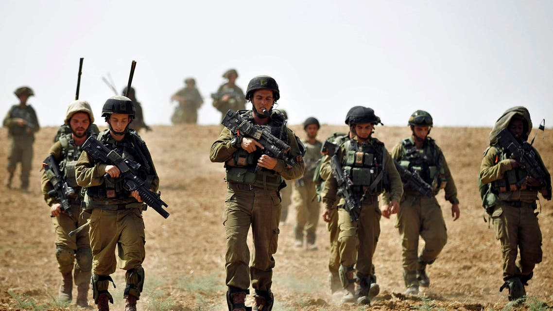 Israeli soldiers from the Nahal Infantry Brigade walk across a field near central Gaza Strip July 12, 2014. reuters