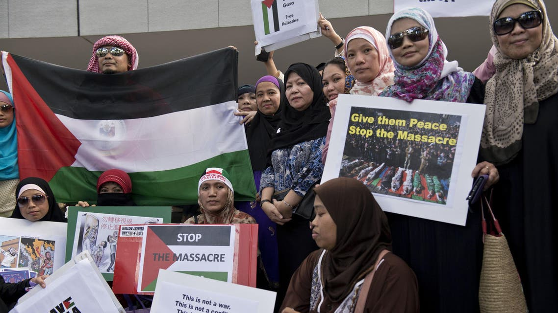 People hold up signs in Hong Kong at a protest against Israel's military campaign in Gaza on July 13, 2014. (AFP)
