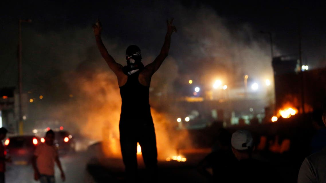 A Palestinian protester gestures during clashes with Israeli troops at a protest against Israeli air strikes on Gaza, at Qalandia checkpoint near the West Bank city of Ramallah July 11, 2014.